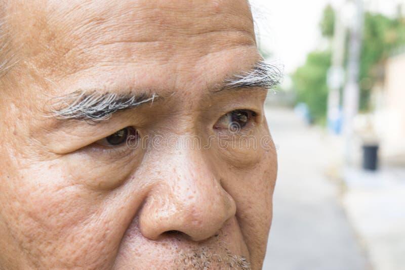 Ojo y ceja asiáticos viejos del ` s del hombre del primer Con el espacio de la copia para el texto fotos de archivo libres de regalías