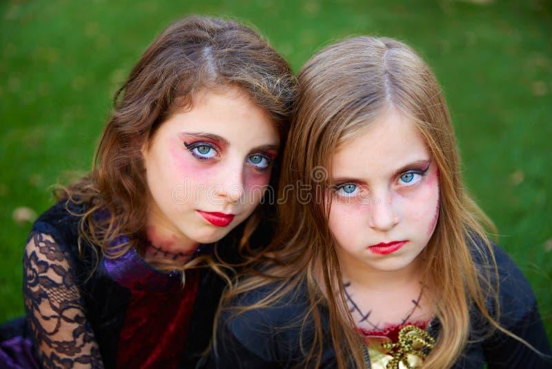 Ojos azules de las muchachas del niño del maquillaje de Halloween en césped al aire libre foto de archivo