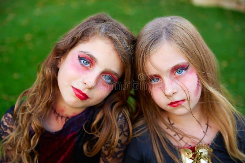 Ojos azules de las muchachas del niño del maquillaje de Halloween en césped al aire libre fotos de archivo