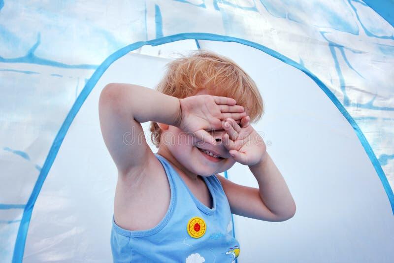 Ojos cerrados del niño juguetón por las manos imagenes de archivo