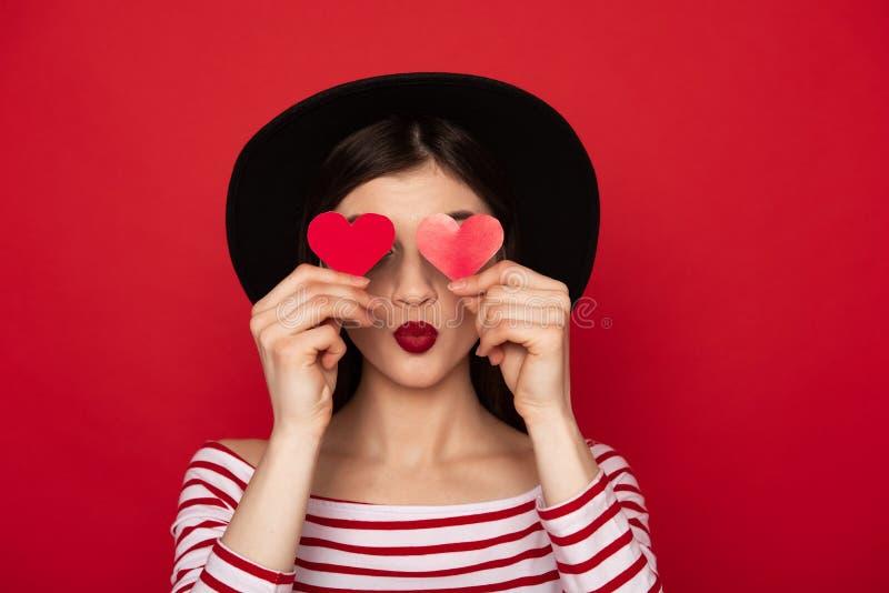 Ojos de cierre de la muchacha coqueta por los corazones de papel rojos imagen de archivo libre de regalías