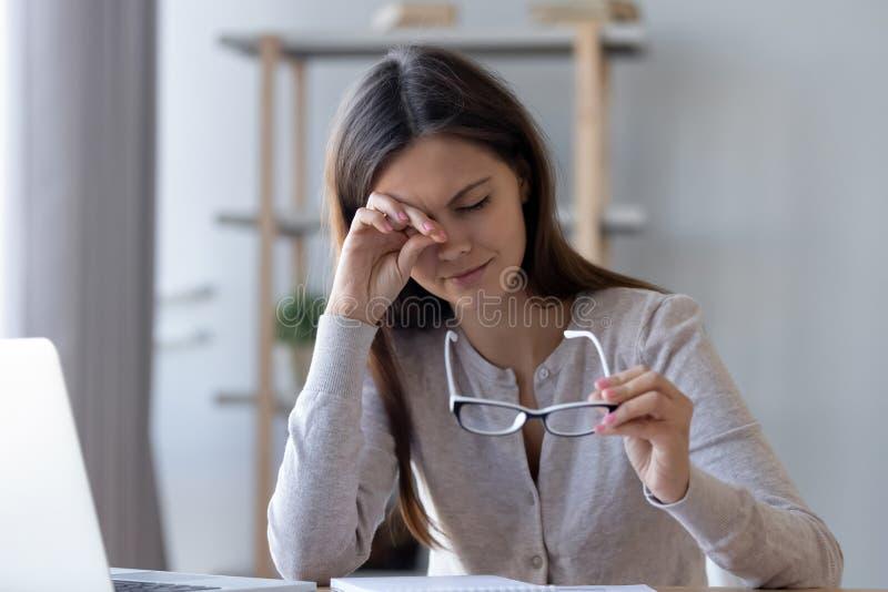 Ojos de frotamiento de la mujer cansada que sienten cansancio del trabajo del ordenador de los vidrios fotografía de archivo