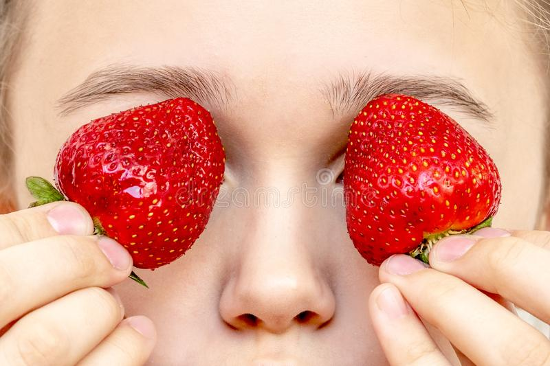Ojos de la fresa Mujer joven hermosa que sostiene las fresas en ojos como los prism?ticos imagenes de archivo