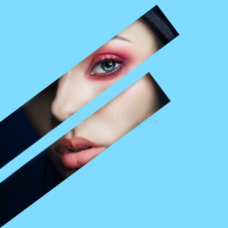 Ojos rojos del maquillaje de la cara de la belleza de una chica joven en un agujero rajado del papel azul Mujer con la sombra que fotos de archivo