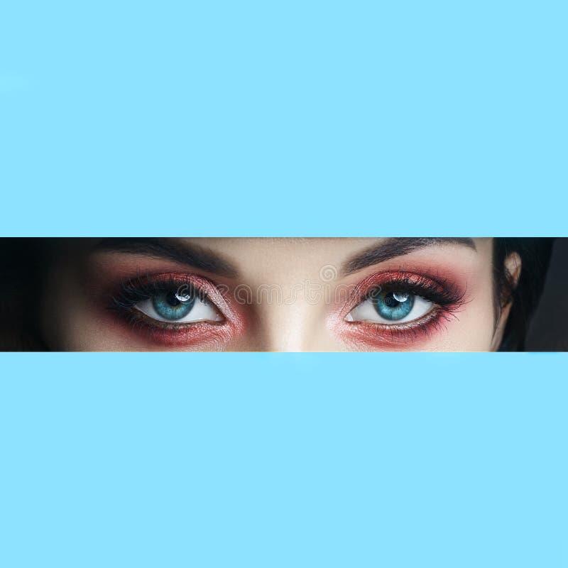 Ojos rojos del maquillaje de la cara de la belleza de una chica joven en un agujero rajado del papel azul Mujer con la sombra que fotografía de archivo