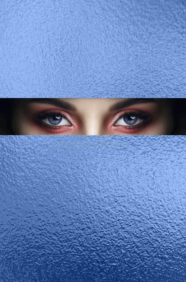 Ojos rojos del maquillaje de la cara de la belleza de una chica joven en un agujero rajado del papel azul Mujer con la sombra que imágenes de archivo libres de regalías