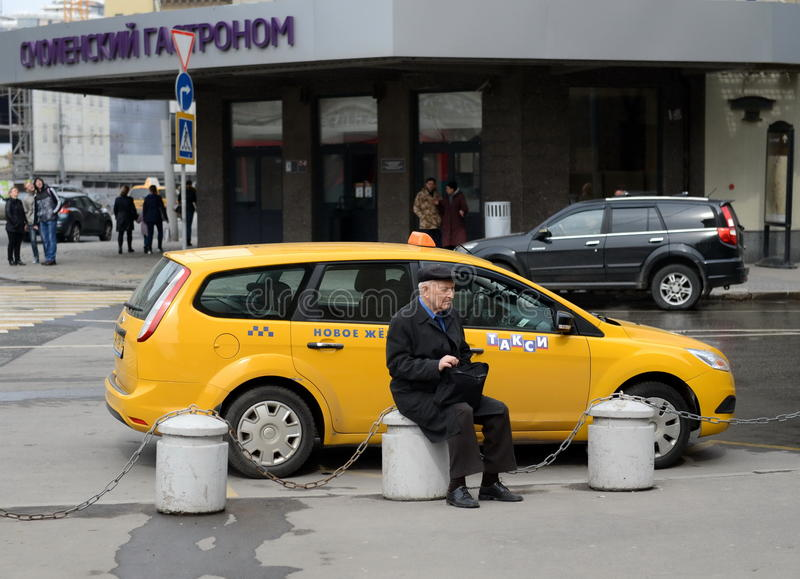 Okänd äldre manantipersonal som vilar på en konkret sockel nära vägen royaltyfri fotografi