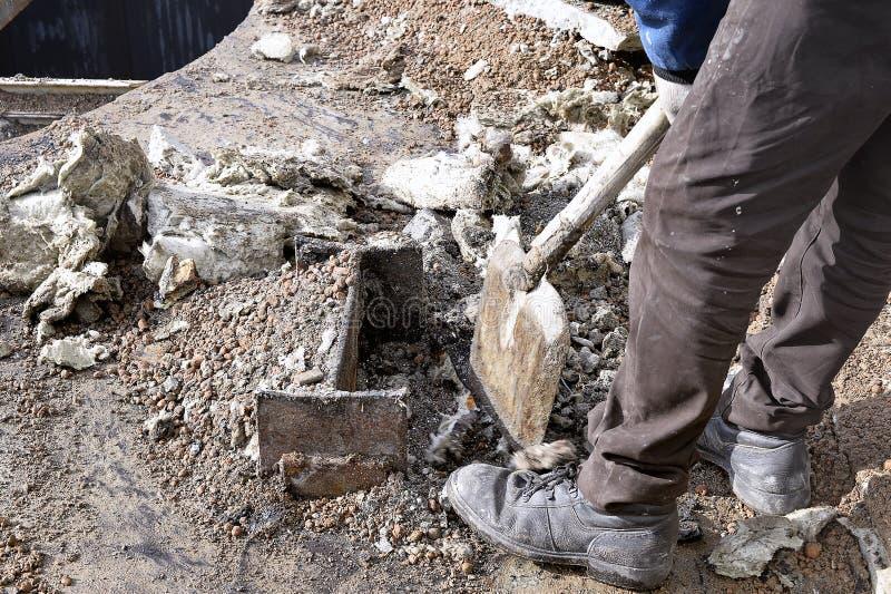 Okänd arbetare med ett skräp för skyffelröjningkonstruktion royaltyfri bild