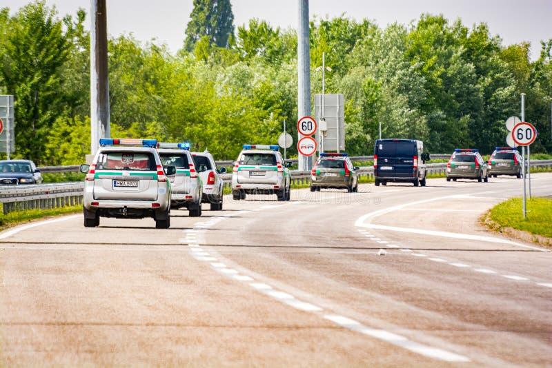 Okänd huvudväg, Ungern - Maj 1, 2017 Eskortfartyg av den polska överskriften för polisbilar till Serbien under flyktingkris royaltyfria bilder