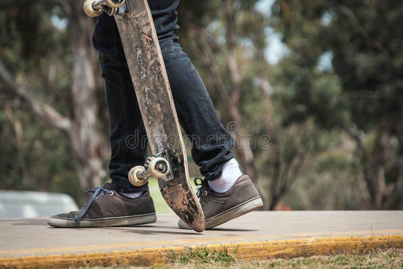 Okänd man som går med skateboarden arkivfoto