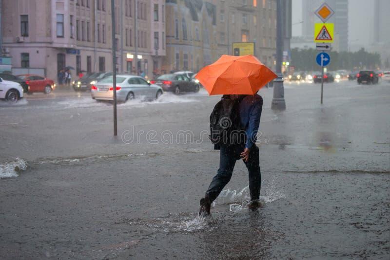 Okänd man som går på en översvämmad gata royaltyfri foto