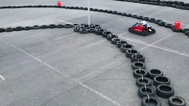 Okända piloter som tävlar i Karting Championship på ett spår av gamla svarta bildäck, flyg Media Personer arkivbilder