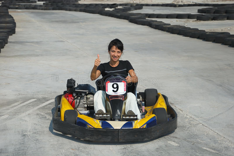 OK. Prety brunette driving a kart on karting circuit royalty free stock photos