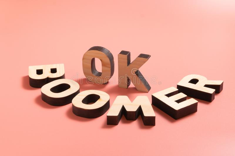 OK Boomer. Internet meme popular among young people. Wooden words on pink background. OK Boomer. Internet meme popular among young people. Wooden letters on stock photos