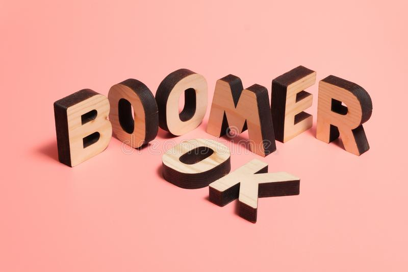 OK Boomer. Internet meme popular among young people. Wooden words on pink background. OK Boomer. Internet meme popular among young people. Wooden letters on royalty free stock photos