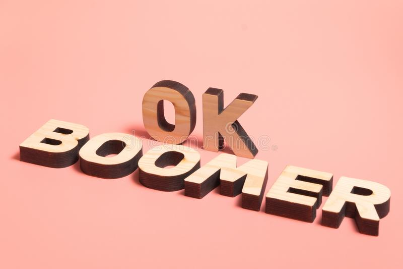OK Boomer. Internet meme popular among young people. Wooden words on pink background. OK Boomer. Internet meme popular among young people. Wooden letters on stock photo