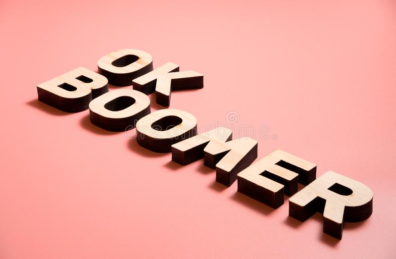 OK Boomer. Internet meme popular among young people. Wooden words on pink background. OK Boomer. Internet meme popular among young people. Wooden letters on stock photography