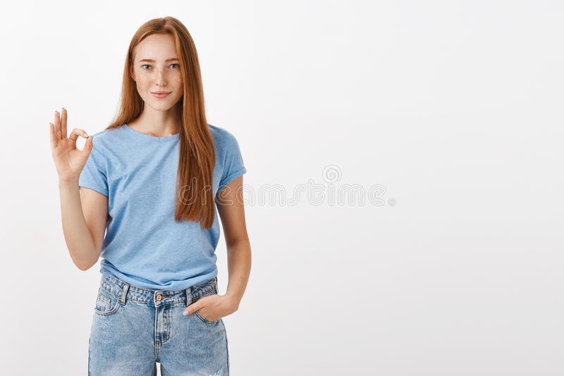 Ok it is deal. Portrait of good-looking satisfied and happy redhead female student in blue t-shirt holding hand in royalty free stock photos