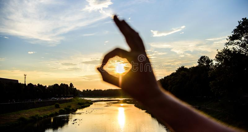 Ok gesture sign of best choice approve and confirm. Silhouette ok hand gesture in front of sunset above river water. Surface. Sunset sunlight romantic stock photo