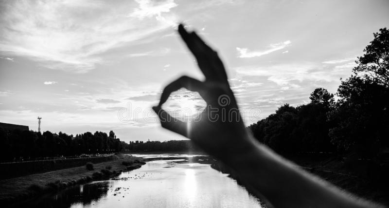 Ok gesture sign of best choice approve and confirm. Silhouette ok hand gesture in front of sunset above river water. Surface. Sunset sunlight romantic royalty free stock image