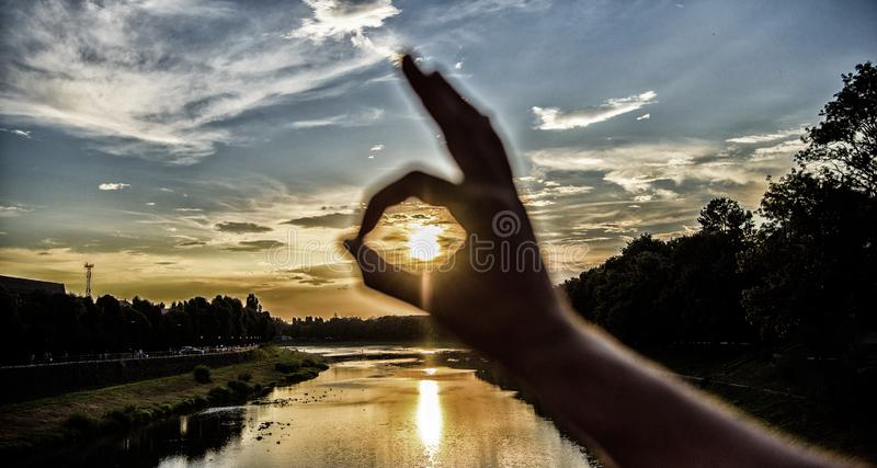 Ok gesture sign of best choice approve and confirm. Silhouette ok hand gesture in front of sunset above river water. Surface. Sunset sunlight romantic royalty free stock photography