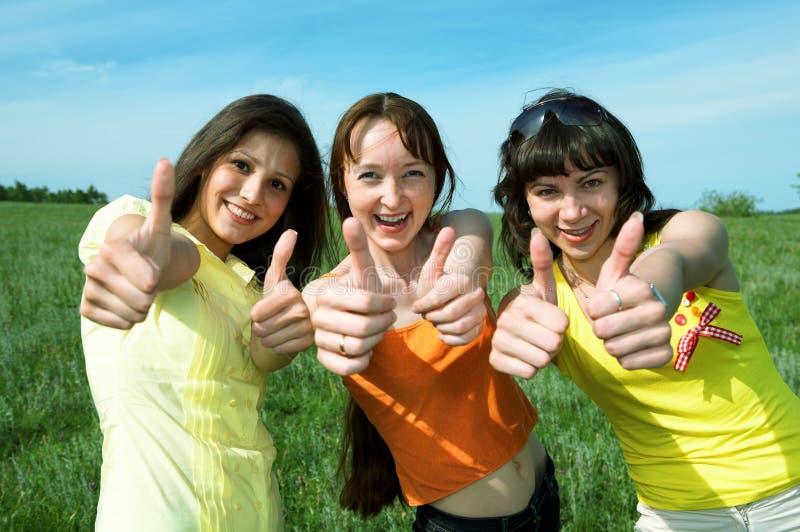 Ok heureux de signe d'exposition de trois amis dans le domaine vert photo stock