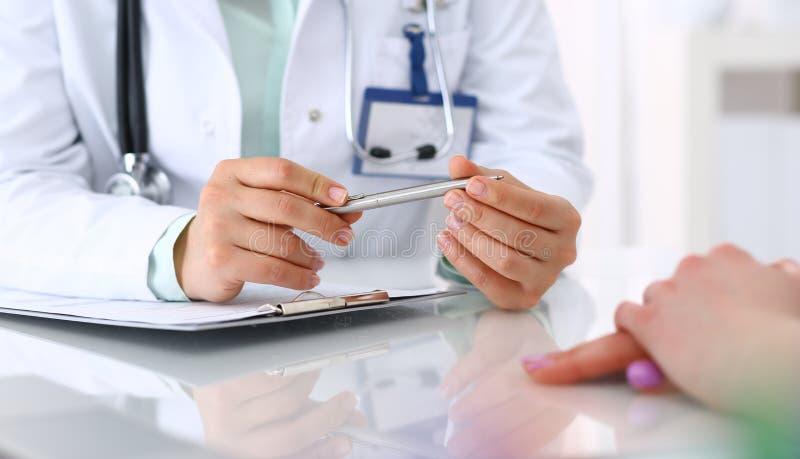 Ok?nd doktor och patient som talar, medan sitta p? skrivbordet i sjukhuskontoret, n?rbild av m?nskliga h?nder Medicin och royaltyfria foton