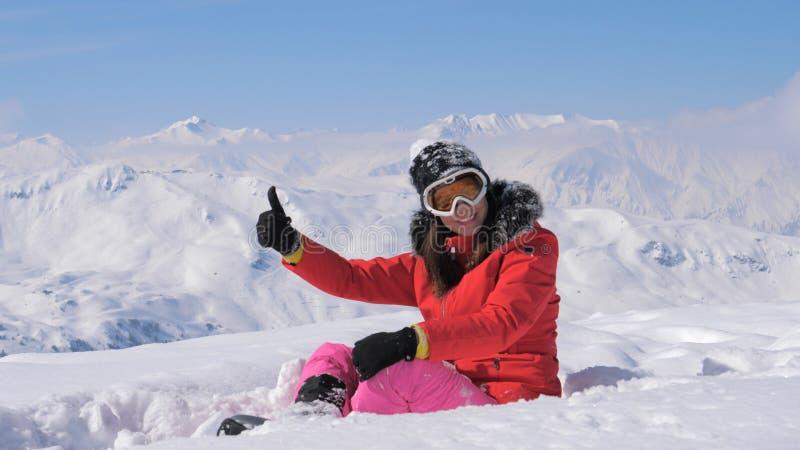 Ok och finger för hand för kvinnaskidåkareshower upp på den snöig bergbakgrunden royaltyfri bild