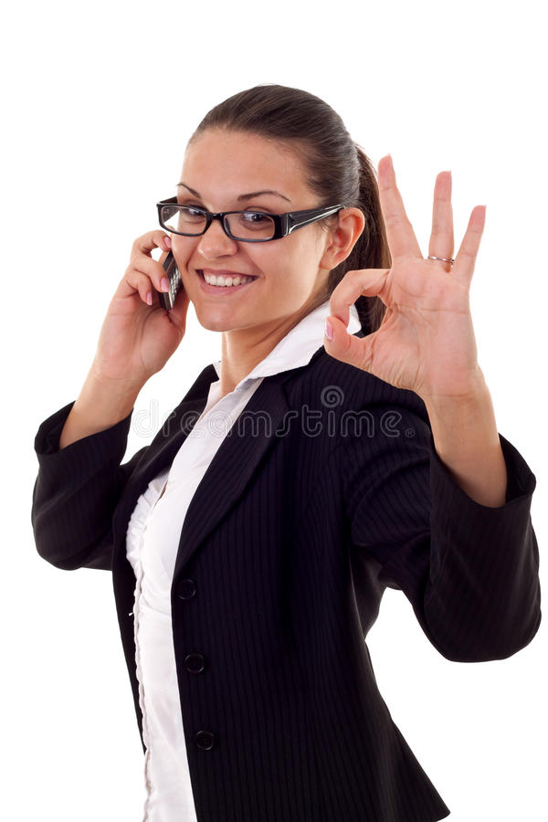 Ok on the phone. Happy business woman with phone and thumbs up gesture, isolated stock image