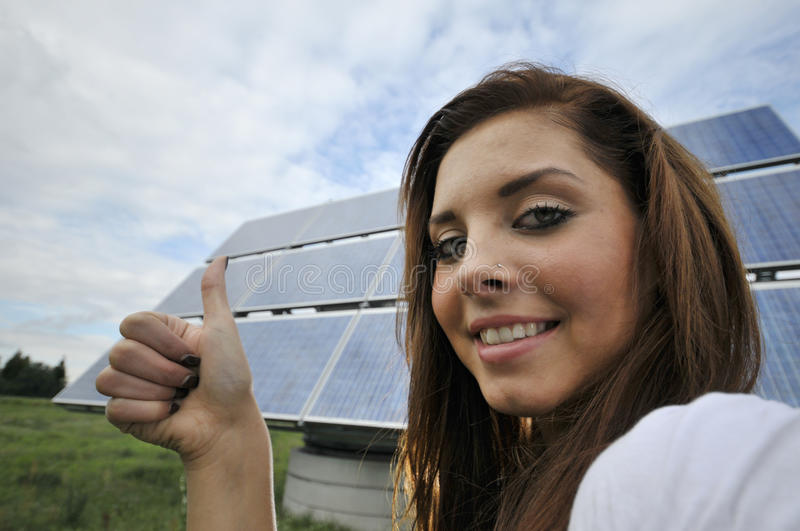Ok for photovoltaics. Portrait of smiling teenager with thumb up in field, solar panel and cloudscape in background royalty free stock image