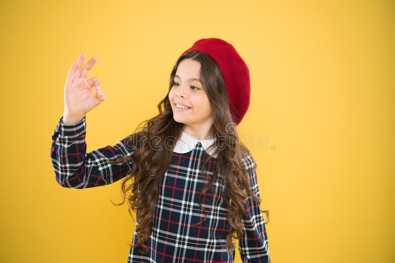 It is ok. small kid with long curly hair. child on yellow background. fashionable school uniform. kid fashion. parisian. Fashion girl. childrens day. happy girl royalty free stock photos