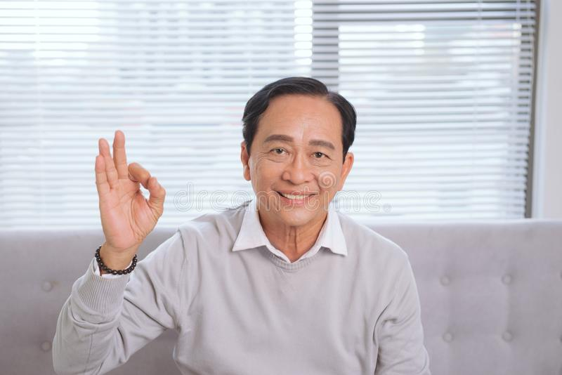 Ok tecken för asiatiska gesthänder för hög man arkivbild