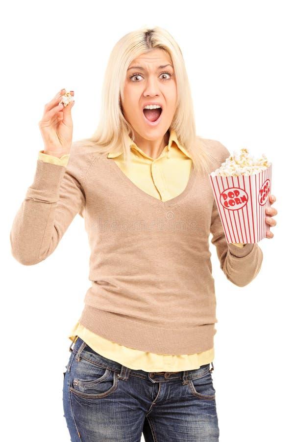 Okaleczająca blond kobieta trzyma popkornu krzyczeć i pudełko