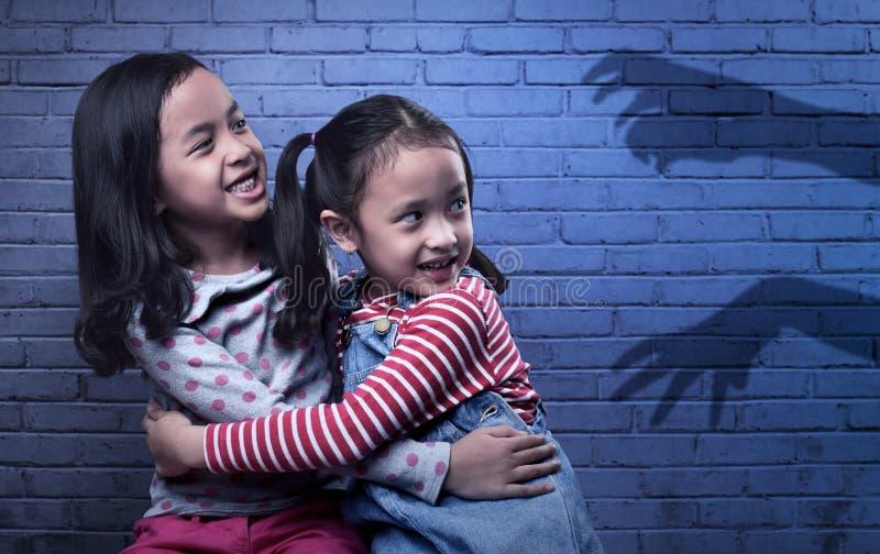 Okaleczająca dwa azjata mała dziewczynka patrzeje czarną duch rękę zdjęcia royalty free