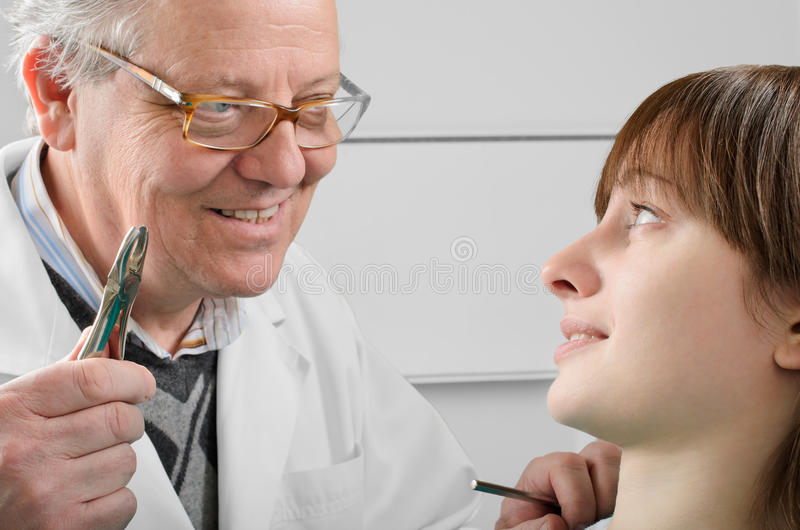 Okaleczająca dziewczyna i zły stary dentysty narządzanie dla ząb ekstrakci fotografia royalty free