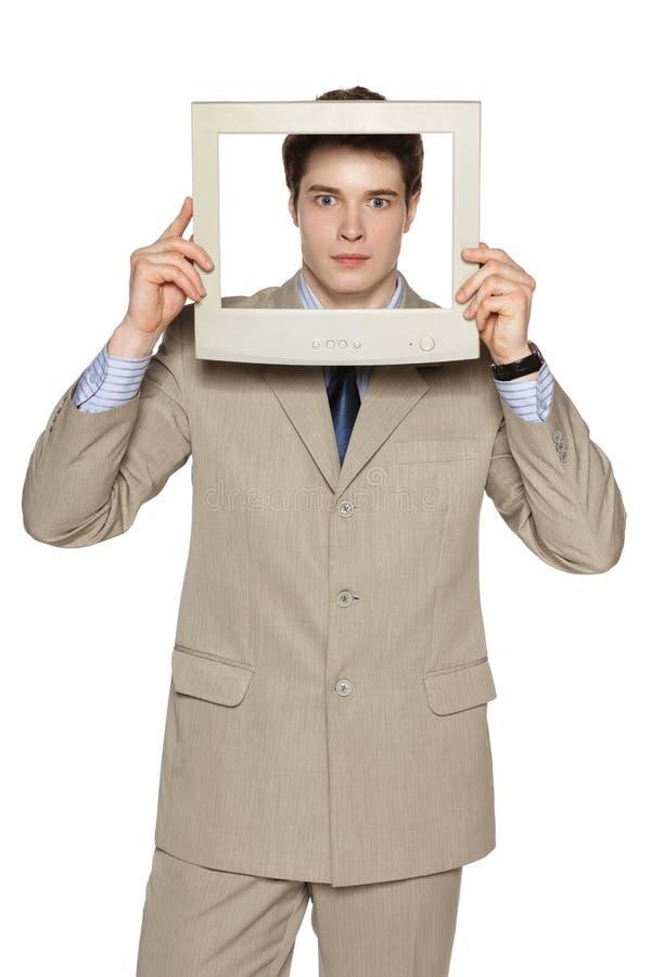 Okaleczający biznesmen patrzeje przez TV, ekranu komputerowego ramy/ zdjęcia royalty free
