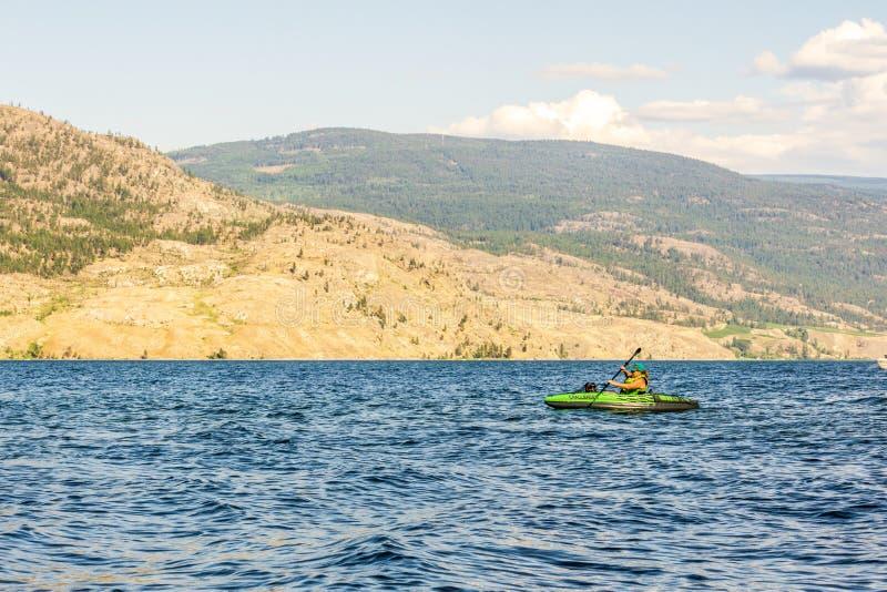 Okanagan dolina Kanada, Sierpień, - 05, 2018: Osoba kayaking na nadmuchiwanym kajaku w Okanagan jeziorze Kanada BC zdjęcia royalty free