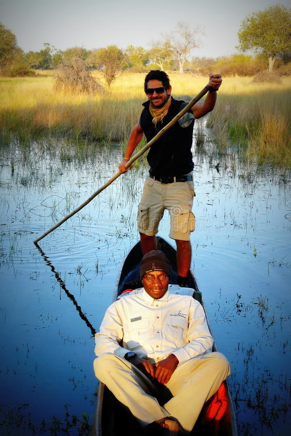 Okavango delta, Botswana - July 14th of 2012: Local guides and tourists ride traditional boats called mokoros seeking for wildlife stock photography