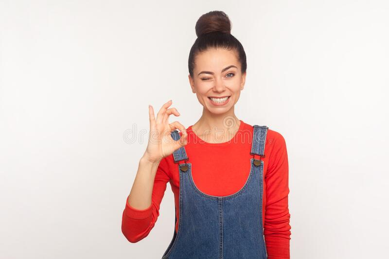 Okay, agree with you! Portrait of cheerful stylish pretty girl with hair bun in denim overalls showing ok hand sign. And winking, approving idea. indoor studio stock images