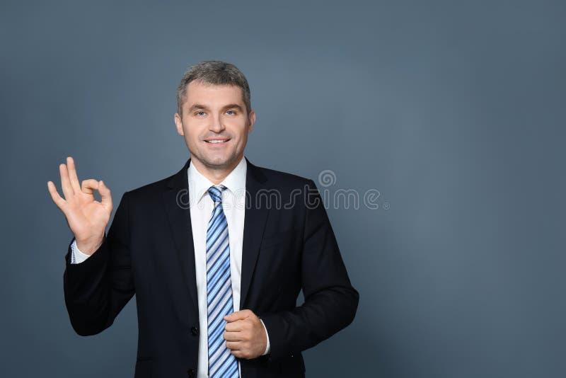 OKAYgeste der hübschen Geschäftsmannvertretung auf grauem Hintergrund stockbild