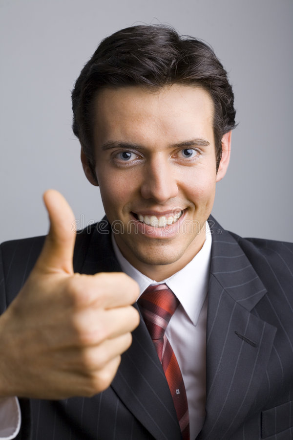 Okey dude. Smiling, handsome businessman with thumb up. Looking at camera. Gray background, front royalty free stock images
