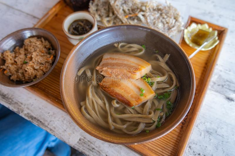 Okinawa Soba noodles with pork soft bone broth. Fire noodles with pork belly and Japanese soup royalty free stock photo