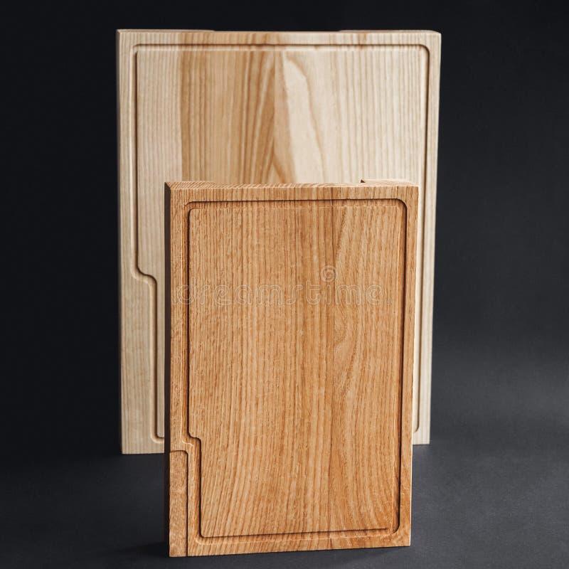 Okkernoot met de hand gemaakte houten scherpe raad op zwarte houten raad royalty-vrije stock afbeeldingen