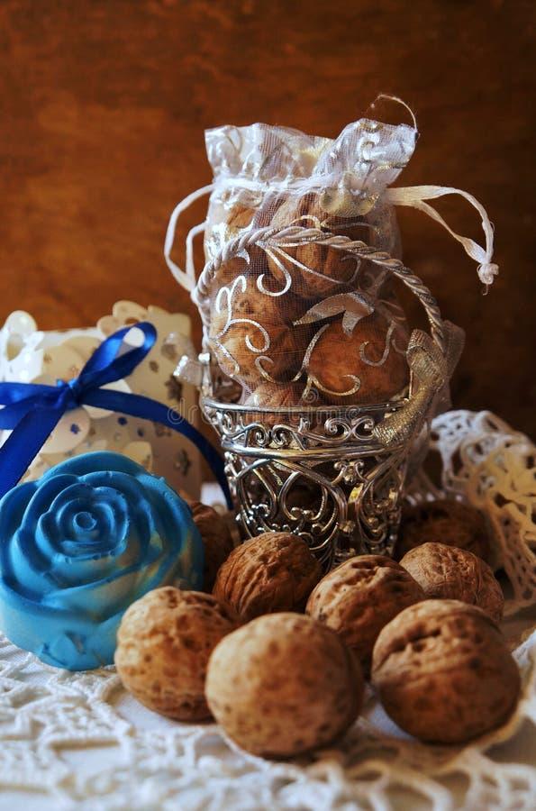 Okkernoten, decoratieve emmer en blauwe bloem! stock foto