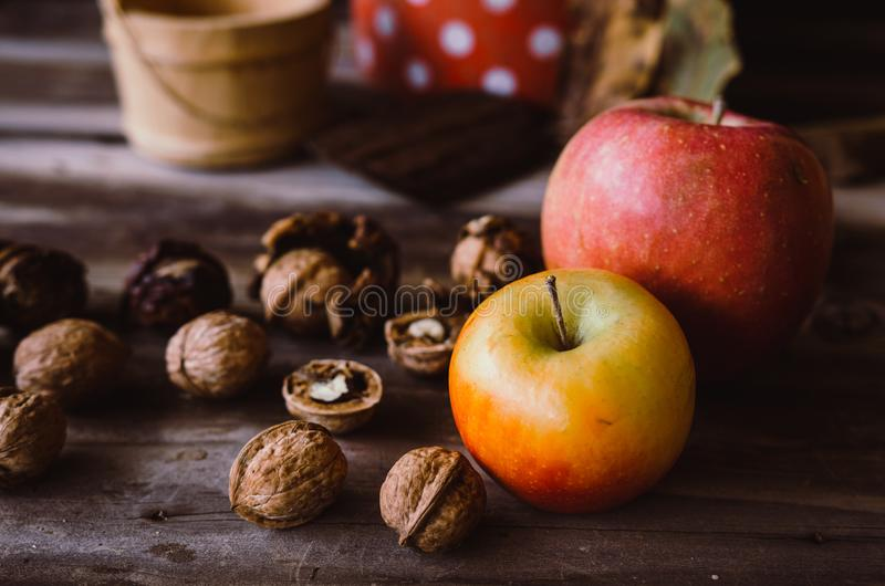Okkernoten en appelen op rustieke lijst met oude details op het royalty-vrije stock afbeeldingen