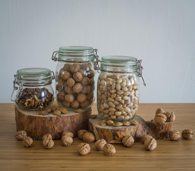 Okkernoten, Gepelde okkernoten, pistaches, paranoten in glaskruik op houten tribune royalty-vrije stock foto