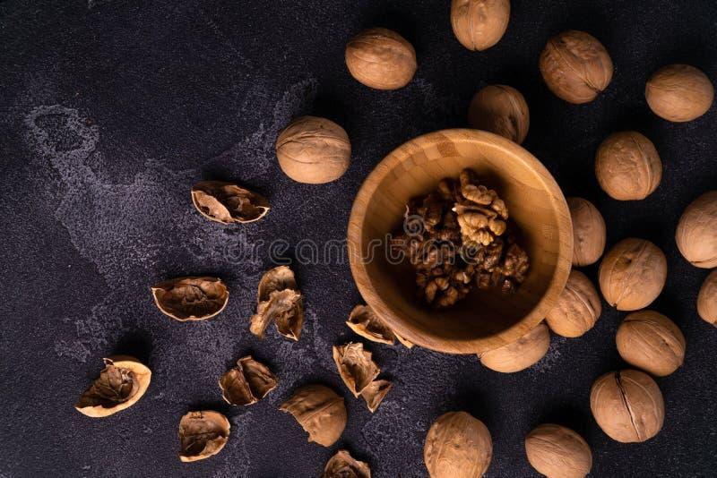 Okkernoten in houten kom en op zwarte leioppervlakte Gezonde noten en zadensamenstelling stock afbeeldingen