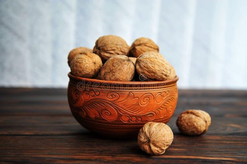 Okkernoten, noten in aardewerk op een houten lijst stock afbeeldingen
