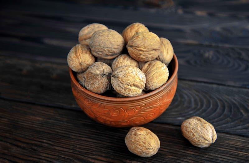Okkernoten, noten in aardewerk unpeeled op de lijst stock foto's