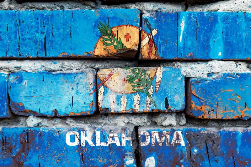Oklahoma grunge, danificado, arranhado, antiga bandeira dos estados unidos na parede de tijolos imagens de stock